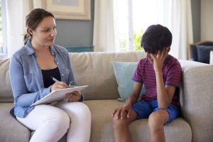 Young boy sitting on the couch with a woman holding a clipboard What is the role of a child psychologist